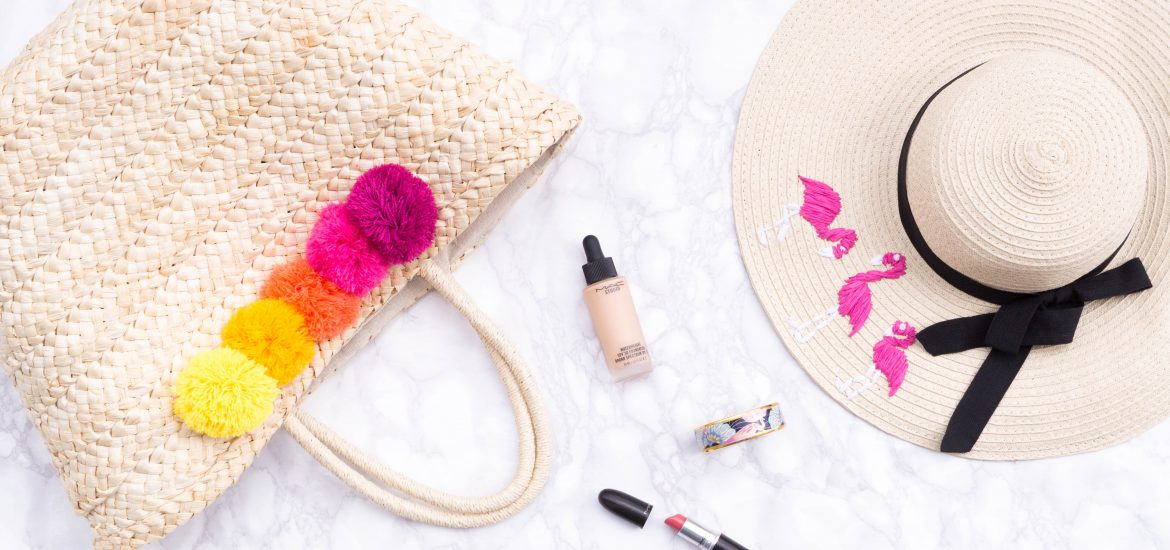 flatlay straw bag hat pompoms makeup